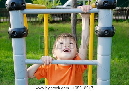 boy climbing stairs and playing outdoors on playground children activity. Child having fun. Active healthy childhood concept