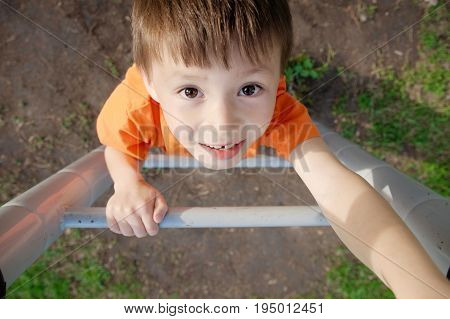 boy climbing stairs and playing outdoors on playground children activity. Child portrait from above. Active healthy childhood concept