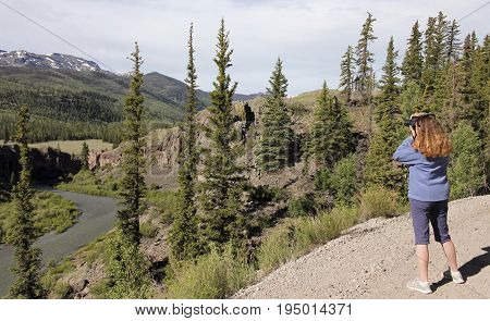 LAKE CITY, COLORADO, JUNE 20. The Alpine Loop Backcountry Byway on June 20, 2017, near Lake City, Colorado. A Woman Shoots Scenic Photos on the Alpine Loop Backcountry Byway in Colorado.
