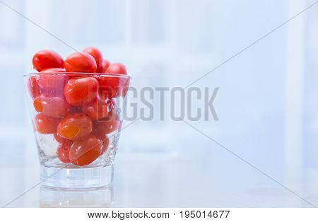 small red cherry tomatoes in wet clear glass cup on white table with blur background concept for healthy diet eating fruit and vegetable heathy food space for text or copy space