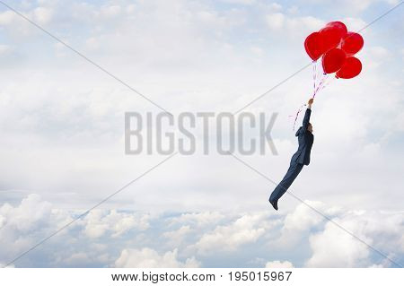 business freedom concept businessman flying in the sky with balloons