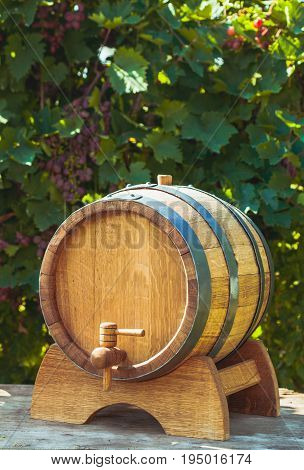 The wooden barrel with wine on a table outdoor. Winery culture