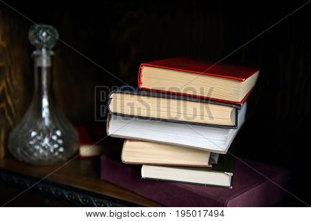 Paper book stacked on a shelf and a decanter of alcohol. Education and intelligence are well-read people. Old gadgets from short stories and novels. The passing of time read.