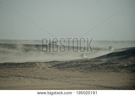 Vehicles racing in desert with sand dust on grey sky background. Safari trip on jeep cars. Barchan dune bashing. Offroad adventure. Extreme activity. Travel and travelling. Summer vacation