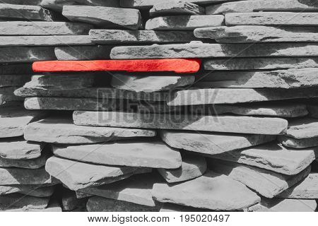 Red stone among the gray stones which are stacked one on the other.