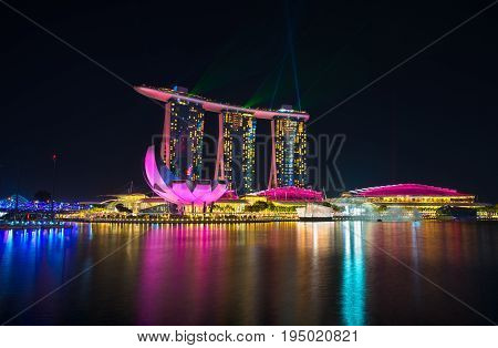 SINGAPORE-JULY 8 2016: Marina Bay Sands at night during beautiful laser light and Water Show at the marina bay waterfront in singapore the most famous tourist attraction in Singapore