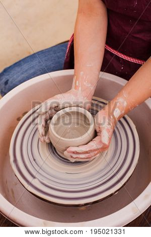 Portrait of girl who tries to make pottery from white clay on a potter's wheel
