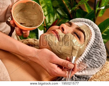 Mud facial mask of woman in spa salon. Massage with clay face in therapy room. Applying beautician with bowl therapeutic procedure on green plants background. Therapeutic mud used in spa procedures.
