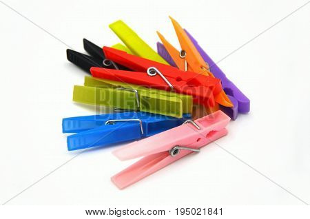 clothes-pegs in many colors on white background