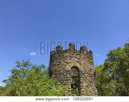 Tower of an ancient fortress. Abandoned old castle tower on the background of blue sky. Copy space for your text