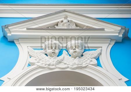 The Faces Of The Angels Above The Stucco Window On The Church Wall
