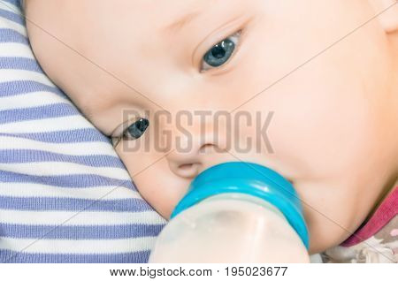 Feeding, The Baby Is Holding A Bottle Of Milk By Hand. Close Up