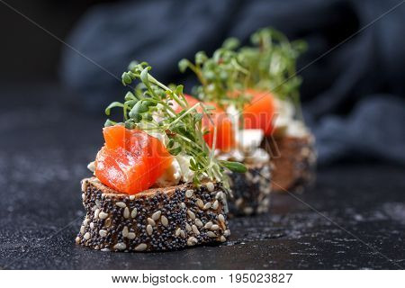 Canape With Salmon And Cheese Cheese On A Dark Background.