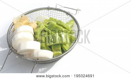 Raw vegetable are gourd and Chinese radish with Ginger soft color In a sieve on white background and has copy space.