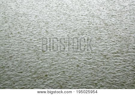 Damaged pond surface during heavy rainfall, background