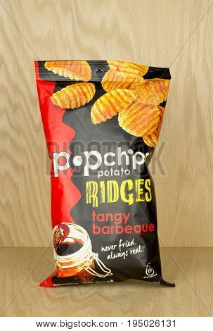 RIVER FALLS,WISCONSIN-JULY 12,2017: A bag of Popchips brand barbecue flavored potato ridges with a wood background.