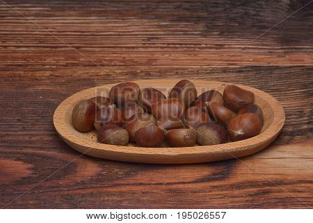 Fresh chestnuts in a bowl on an old wooden table. Group of chestnuts. Chestnuts - fruits horse chestnut - Aesculus hippocastanum. Dark background. Autumn background. Selective focus.
