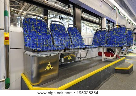 Modern tram inside, city transportation interior with blue seats in row, chrome handles for standing passengers, bright lights and air conditioner