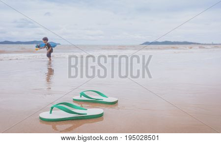 Little boy is playing on the beach with sandals off