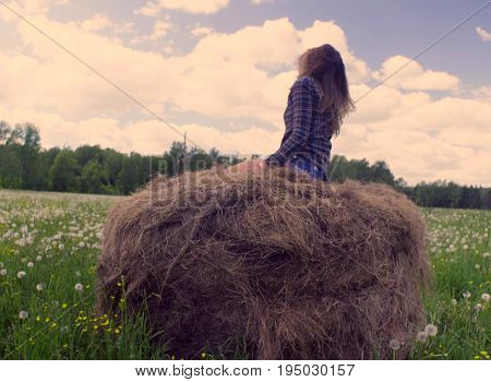 Happy young woman running and jumping on the haystack and laughing. Then she falling down from haystack with somersault