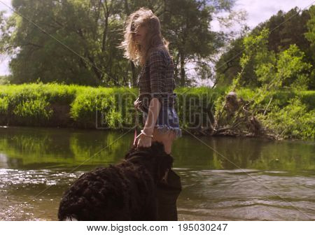 Woman in shorts and waders with a dog walking through the river