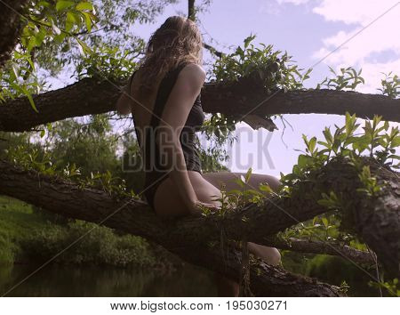 Young woman in a black bathing suit sitting on a tree branch over a river