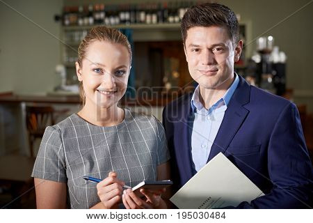 Portrait Of Owner With Waitress In Restaurant