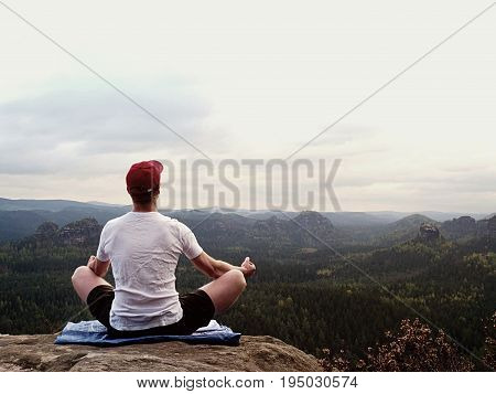 Yoga Practicing  At Mountain Summit With Aerial View Of The Mountain Valley. Tall Sportsman Practici