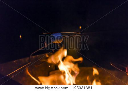 Marshmallow Being Roasted Over A Campfire On A Dark Summer Evening