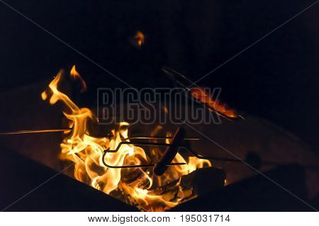 Hot Dogs Being Roasted Over A Campfire Pit On A Dark Summer Evening