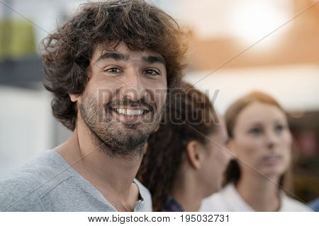 Portrait of cheerful guy in office with workmates