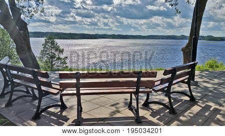 A lonely bench overlooking the lake on a summer sunny day