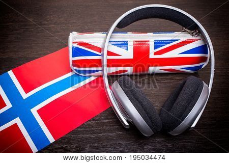 Headphones with UK flag pencil case with Norwegian flag concept on wooden background