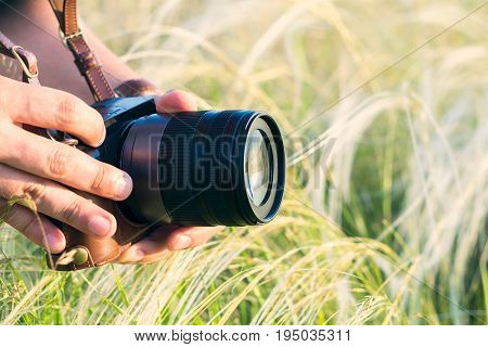 The digital DSLR camera in a hand. Male hands with camera take photo of green grass