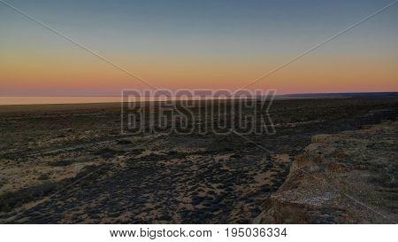 Panorama view to Aral sea from the rim of Plateau Ustyurt near Aktumsuk cape at sunset in Karakalpakstan Uzbekistan
