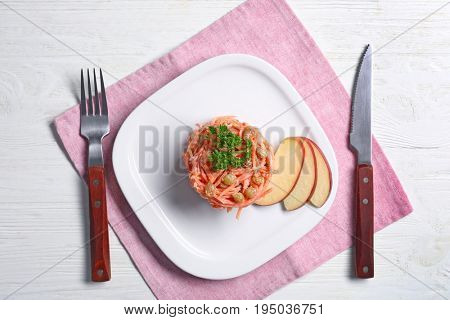 Square plate with yummy carrot raisin salad on pink napkin, top view