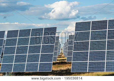 The outgoing rows of photovoltaic panels of solar power plants with a cloudy sky