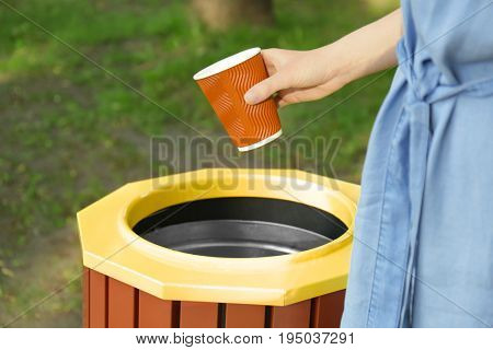 Young woman throwing plastic cup in litter bin outdoors, closeup
