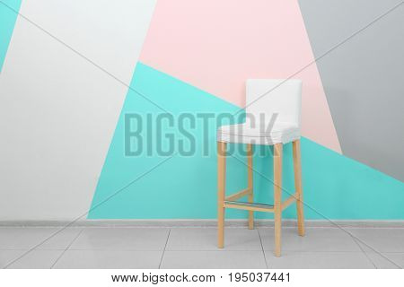 Trendy chair near wall with mint color