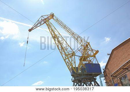 Hoisting crane against blue sky