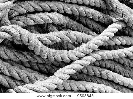 A well used and worn rope lays in a pile ready for its next use.