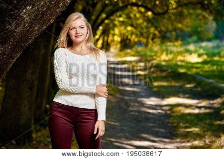 Pretty young blonde woman in autumn park on sunny day