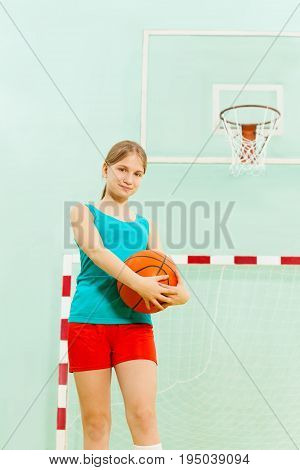 One Caucasian teenage girl, basketball player, holding ball standing in school gymnasium
