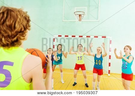 Portrait of basketball player throwing the ball into the basket while his opponents defending the hoop