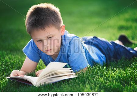 Boy reading book, lying down on green grass. Late afternoon light from behind with selective focus on boys eyes.