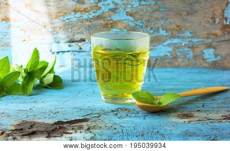 glass of herbal Melissa mint tea on a wooden table. Melissa mint tea in a transparent cup mint flowers on wooden table. Herbal tea for baby's stomach pain in the abdomen. Calming. Copyspace.