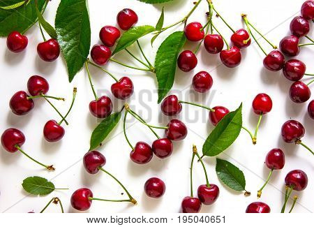 Sweet ripe fresh cherries background. Scattered cherries on white pattern with copy space. Cherry fruit backround. Garden fresh organic cherries at wooden table top view. Food background.