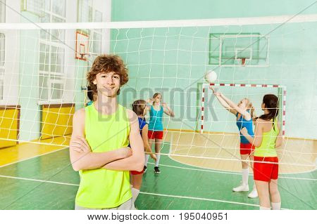 Portrait of teenage boy in sportswear standing next to the volleyball net in gymnasium