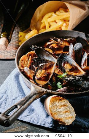 Shell mussels in a frying pan in tomato sauce, French fries and croutons on a dark background