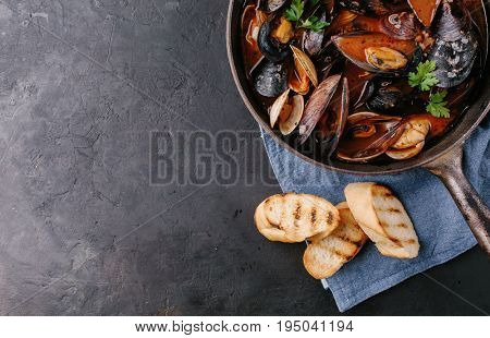 Mussels in a frying pan in tomato sauce and croutons on a dark background. Top view. Copy space.